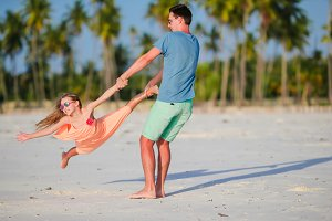 Happy father and his adorable little daughter at tropical beach. Caucasian family having fun together on suumer vacation on white beach running and enjoying their holidays
