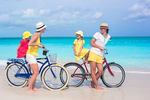Young family of four riding bicycles on a tropical sand beach