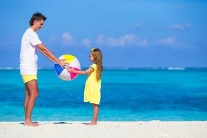 Happy father and daughter playing with ball having fun outdoor on beach