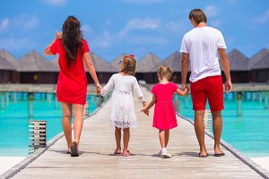 Back view of beautiful family on wooden jetty during summer vacation at luxury resort