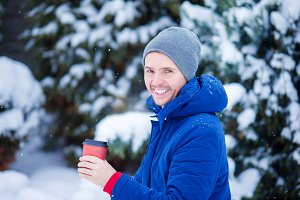 Young caucasian man drinking coffee in cold winter day outdoors