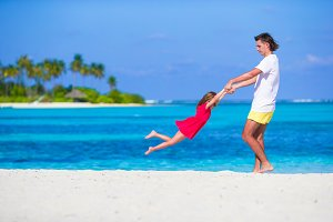 Little cute girl and dad during tropical beach vacation