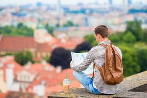 Young man with a city map and backpack background european city. Caucasian tourist looking at the map of European city with beautiful view of attractions.