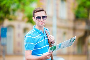 Young man in sunglasses with a city map and backpack in Europe. Caucasian tourist looking at the map of European city in search of attractions.