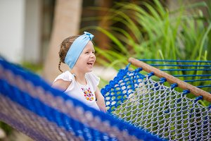Adorable little girl swinging in hammock at beach