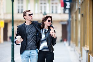 Romantic couple walking together in Europe. Happy lovers enjoying cityscape with famous landmarks. Stylish urban young man with hot coffee and woman in hat on travel in Prague