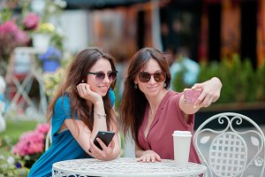 Two young girls taking selfie with smart phone at the outdoors cafe. Two women after shopping with bags sitting in openair cafe with coffee and using smartphone