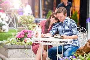 Restaurant tourists couple eating at outdoor cafe. Young woman enjoy time with her husband, while man reading.