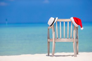 Beach chair with red Santa and straw hat background beautiful turquoise sea