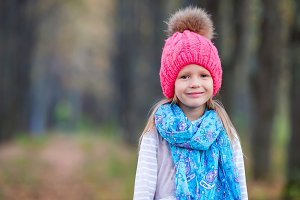 Portrait of little girl at beautiful autumn day outdoors