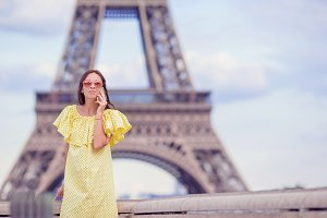 Young woman talking by phone background Eiffel Tower in Paris
