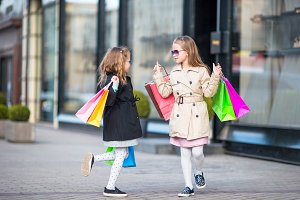 Adorable little girls on shopping. Portrait of kids with shopping bags.