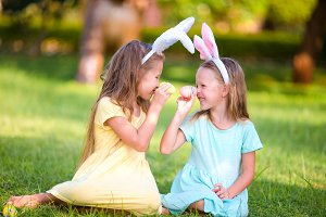 Two adorable little sisters playing with eggs wearing bunny ears on Easter day