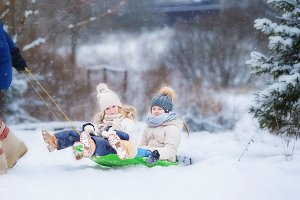 Little girls enjoy a sleigh ride. Child sledding. Children play outdoors in snow. Family vacation on Christmas eve outdoors