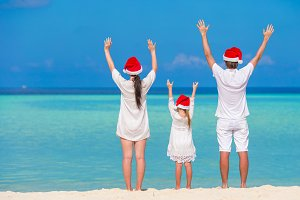 Happy family of three in Santa Hats during Christmas tropical vacation