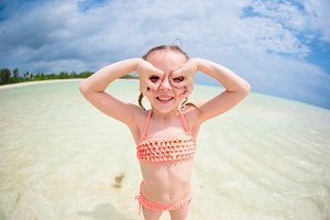Adorable little girl having fun like as a superhero at beach during summer vacation