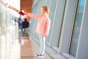 Little girl with boarding pass in airport waiting for flight