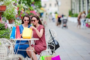 Two fashion colorful shoppers with bags shopping with a smart phone in the street. Sale, consumerism and people concept. Caucasian girls enjoy their warm day in outdoor cafe.