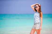 Young beautiful woman enjoying the music on white beach