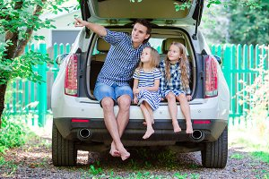 Father with kids sitting in car while traveling