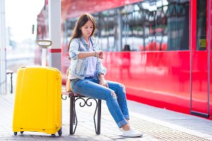 Young woman with luggage on train platform waiting for aeroexpress