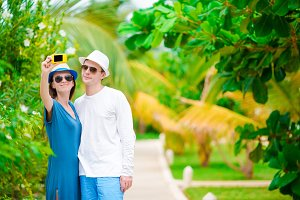Young happy couple making selfie with mobile phone on tropical vacation