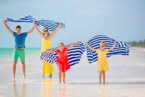 Happy family having fun running with towel and enjoying vacation on tropical beach with white sand and turquoise ocean water