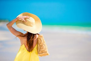 Back view of woman in big hat during tropical beach vacation