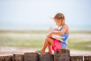Little adorable girl reading book during tropical white beach