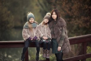 Adorable little girls with mother in autumn park outdoors