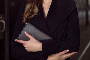 woman hold black purse clutch bag