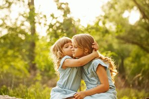 Two cute little sisters. Kiss