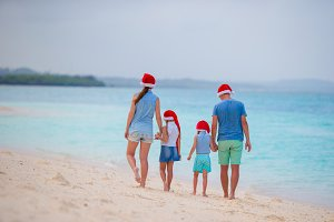 Happy family with two kids in Santa Hats on summer vacation. Christmas holidays with young family of four enjoying their sea trip