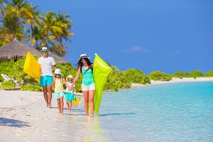 Happy beautiful family on white beach with air mattresses and kids toys