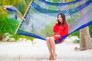 Beautiful woman relaxing at hammock on tropical beach