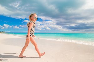 Adorable little girl at shallow water on the beach