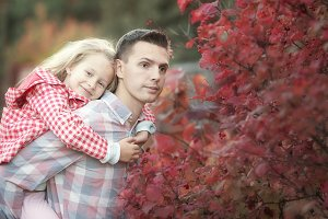 Little adorable girl with dad in autumn park at warm day