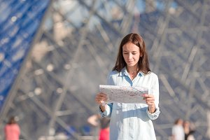 Young woman with map in european city outdoors