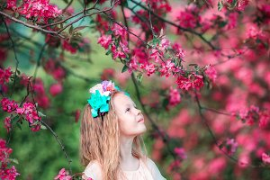 Adorable little girl in beautiful blooming apple garden outdoors