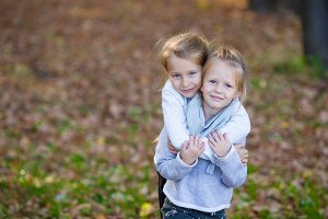 Little girls having fun in beautiful autumn park outdoor