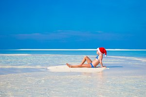 Little cute girl in Santa hat on white beach during vacation