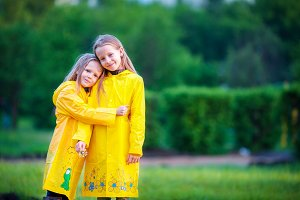 Funny cute toddler girls wearing waterproof coat playing outdoors by rainy and sunny day