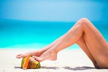Slim woman applying sunscreen on her legs, sitting on sandy beach with sea background