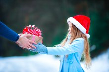 Christmas concept. Little girl giving a New Year's gift on Xmas eve