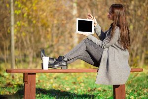 Beautiful girl with laptop in autumn park outdoors