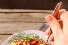 Homemade Italian pasta with chanterelle mushrooms on dark stone background. Woman's hand with a fork