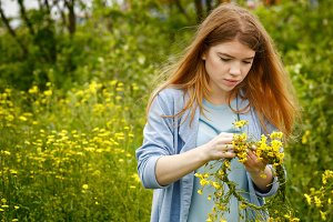 Girl weaves wreath of wildflowers