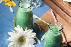 Green smoothie in glass bottles
