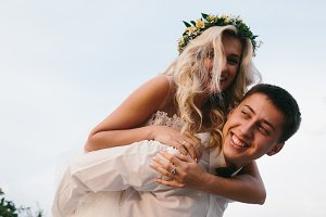 groom carries bride on his back outdoors