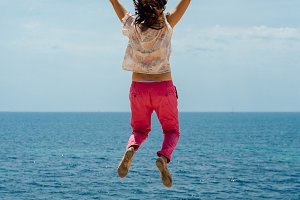 Happy woman jumping against sea